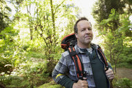 Portrait smiling man hiking with backpack in woods - HEROF32398