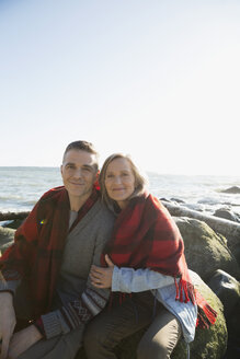 Portrait affectionate couple wrapped in blanket hugging on sunny beach rocks - HEROF32416