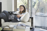 Portrait confident woman reading magazine and drinking wine in sunny living room - HEROF32425