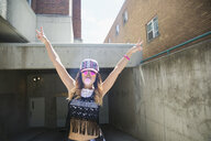 Portrait exuberant cool young woman at urban parking garage entrance - HEROF32470