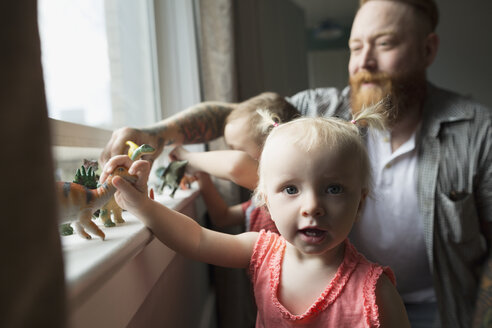 Portrait daughter and father playing with toy dinosaurs at windowsill - HEROF32521
