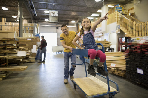 Playful father pushing daughter on cart in home improvement store - HEROF32542