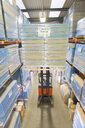 Warehouse worker moving boxes on forklift - JUIF00616