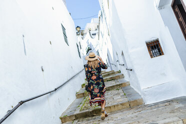 Spain, Cadiz, Vejer de la Frontera, back view of fashionable woman walking through an alley - KIJF02450