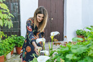 Spain, Cadiz, Vejer de la Frontera, fashionable woman looking at Callas at patio - KIJF02453