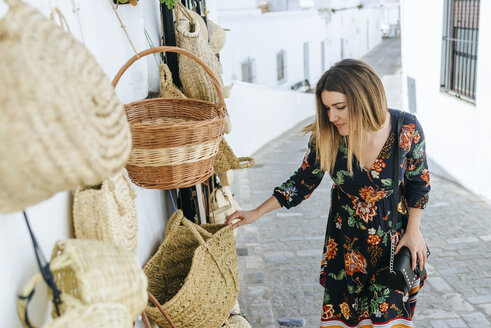 Spain, Cadiz, Vejer de la Frontera, fashionable woman looking at bags and baskets at a shop - KIJF02456