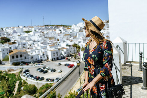 Spain, Cadiz, Vejer de la Frontera, fashionable woman standing on roof terrace looking at view - KIJF02462