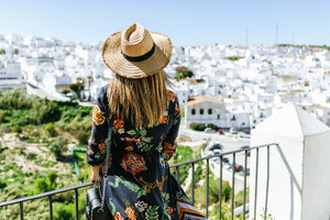 Spain, Cadiz, Vejer de la Frontera, back view of fashionable woman on roof terrace looking at view - KIJF02465