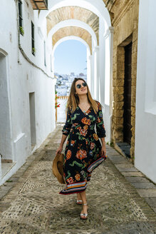 Spain, Cadiz, Vejer de la Frontera, fashionable woman walking through passage - KIJF02468