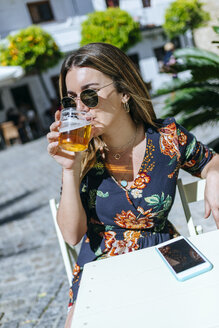 Spain, Cadiz, Vejer de la Frontera, young woman sitting at street cafe drinking glass of beer - KIJF02471