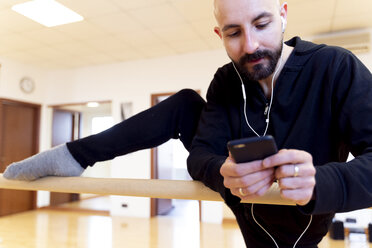 Ballet dancer stretching and using cell phone in ballet studio - FMOF00462