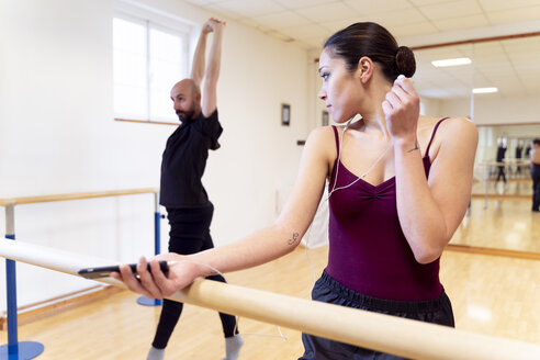 Dancing couple warming up in ballet studio - FMOF00465