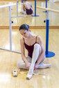 Ballet dancer putting on shoes - FMOF00468