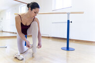 Ballet dancer putting on shoes - FMOF00471