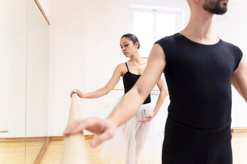 Dancing couple exercising at barre in ballet studio - FMOF00477