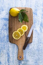 Lemon slices and whole lemon on wooden board with kitchen knife - GIOF05887