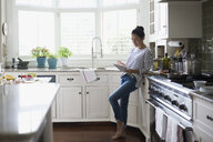 Woman using digital tablet for recipe in kitchen - HEROF32594