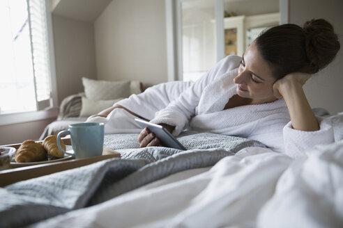Woman in bathrobe using digital tablet on bed - HEROF32609