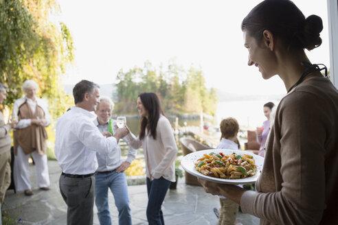 Woman serving food on patio - HEROF32615