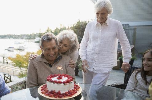 Wife hugging husband with strawberry birthday cake patio - HEROF32618