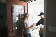Woman signing for delivery at front door - HEROF32627