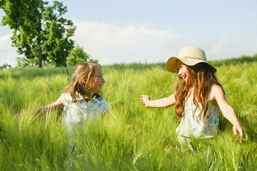 Happy, carefree sisters in sunny, idyllic rural green wheat field - FSIF03792