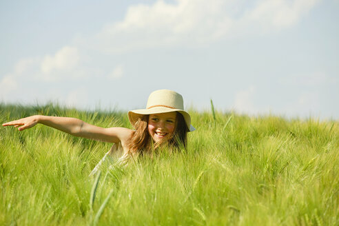 Carefree, happy girl in sunny rural green wheat field - FSIF03795