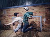 Modern dancers performing against brick wall - FSIF03810