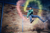 Portrait male modern dancer performing with spray paint against brick wall - FSIF03819