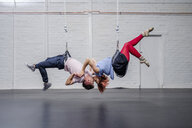 Modern aerialist dancers performing, hanging upside-down and kissing - FSIF03825