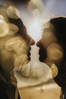 Golden light illuminating silhouetted profile of couple kissing - FSIF03861