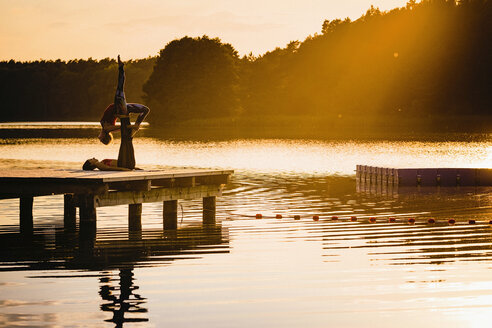 Women practicing acro yoga on lakeside dock at sunset - FSIF03888