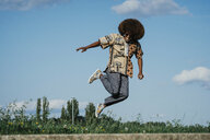 Carefree young man with afro jumping for joy - FSIF03897