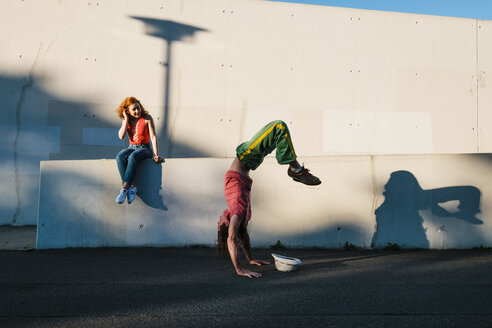 Young woman watching man do handstand along urban wall - FSIF03924