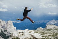 Carefree boy jumping over rocks on mountain, Drei Zinnen Nature Park, South Tyrol, Italy - FSIF03930