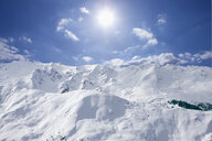View of snowy mountain range and sun in blue sky - JUIF00668