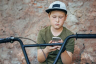 Boy with bmx bike using cell phone - VPIF01202