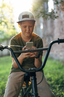 Boy with bmx bike using cell phone - VPIF01205