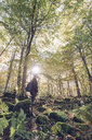 Spain, Navarra, Irati Forest, young woman standing in lush forest - RSGF00134