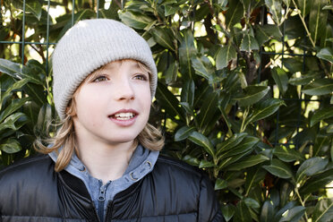 Portrait of boy wearing wooly hat at a hedge - EYAF00066