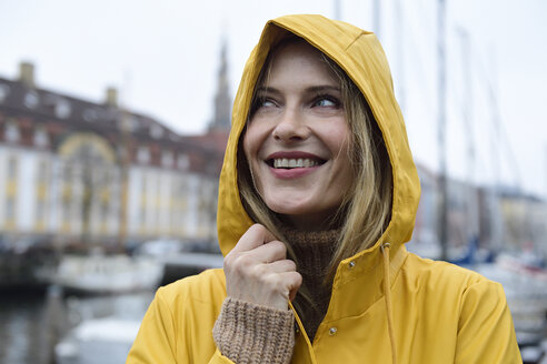 Denmark, Copenhagen, portrait of happy woman at city harbour in rainy weather - ECPF00628