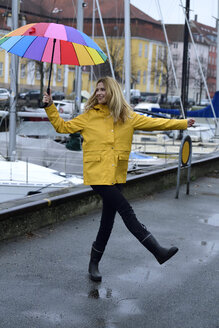 Denmark, Copenhagen, happy woman with colourful umbrella at city harbour - ECPF00637