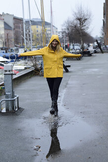 Denmark, Copenhagen, happy woman jumping in puddles at city harbour - ECPF00640