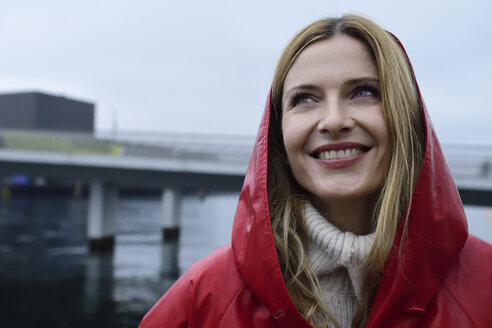 Denmark, Copenhagen, portrait of happy woman at the waterfront in rainy weather - ECPF00658