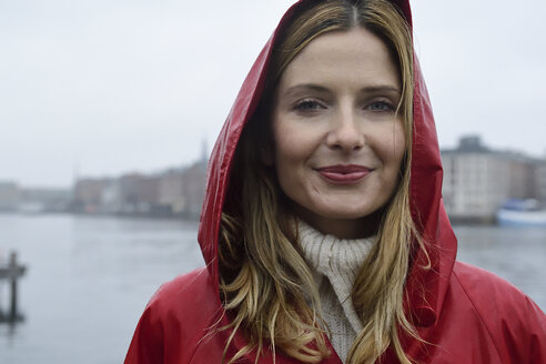 Denmark, Copenhagen, portrait of smiling woman at the waterfront in rainy weather - ECPF00664