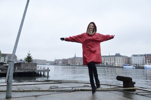 Denmark, Copenhagen, happy woman jumping at the waterfront in rainy weather - ECPF00670