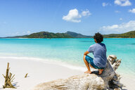 Australia, Queensland, Whitsunday Island, man crouching on log at Whitehaven Beach - KIJF02483