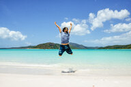 Australia, Queensland, Whitsunday Island, carefree man jumping at Whitehaven Beach - KIJF02486