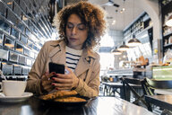 Woman using cell phone in a cafe - FMOF00484
