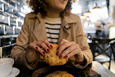 Close-up of woman eating cake in a cafe - FMOF00487